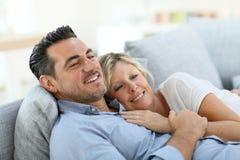 成熟夫妇扭角羚在感到的沙发的休息平静 图库摄影