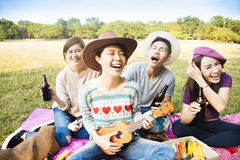 享受野餐和演奏尤克里里琴的年轻朋友 免版税库存照片