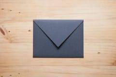 在木书桌上的一个灰色信封, 免版税库存图片