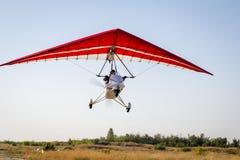 腾飞在蓝天的动力化的悬挂式滑翔机 免版税库存照片