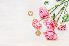 桃红色玫瑰和圆的标志与消息您的和心脏在白色木背景,顶视图 库存图片