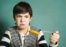 有大汤匙的青春期前的英俊的男孩南瓜汤 库存图片