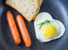 在心形,烤香肠,面包,新鲜的莳萝,顶视图的早餐煎蛋,在平底锅,黑暗的背景 库存图片