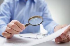 与放大镜读书文件的商人 免版税库存图片