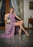摆在葡萄酒风景的一件长的桃红色礼服的美丽的女孩 穿庄重装束的年轻华美的妇女坐扶手椅子 免版税库存图片