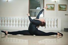 做在大理石地板上的优美的芭蕾舞女演员分裂 执行在光滑的地板上的华美的跳芭蕾舞者分裂 库存图片