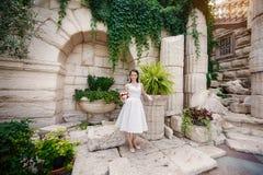 有花束的新娘在与专栏的古老建筑学附近 图库摄影