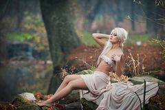 Симпатичная молодая дама сидя около реки в заколдованных древесинах Чувственная блондинка при белые одежды представляя провокацио Стоковая Фотография