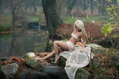 坐在河附近的可爱的小姐在被迷惑的森林 有诱惑摆在秋季公园的白色衣裳的肉欲的金发碧眼的女人 免版税库存照片