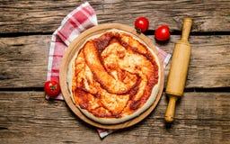 Η ξεδιπλωμένη ζύμη πιτσών με τη σάλτσα ντοματών και με μια κυλώντας καρφίτσα στο ύφασμα Στοκ Εικόνες