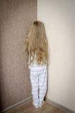 淘气小女孩在被惩罚的角落站立 库存图片