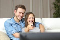 愉快的在电视的夫妇改变的渠道 图库摄影