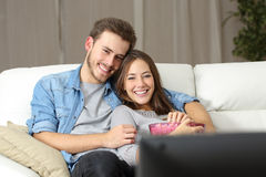 愉快的在电视的夫妇观看的电影 免版税库存照片