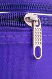拉扯一个拉链的选项和链子在紫罗兰色手提箱的 免版税库存照片