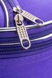 拉扯一个拉链的选项和链子在紫罗兰色手提箱的 库存照片