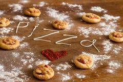微型薄饼用香肠和乳酪在木桌上 免版税库存图片