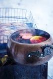 葡萄酒杓子用在火的热的被仔细考虑的酒 免版税库存照片