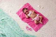 戴比基尼泳装和太阳镜的新出生的女婴 免版税图库摄影