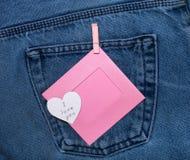 与题字我爱你和桃红色照片框架的纸心脏 在牛仔裤背景的浪漫爱题材 免版税库存照片