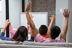 愉快的家庭欣喜,当看在沙发时的电视 免版税库存图片