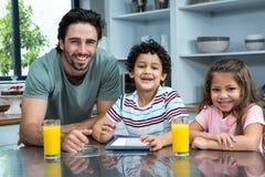 使用片剂的微笑的父亲和孩子 图库摄影