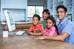 使用计算机的愉快的家庭在厨房里 免版税图库摄影