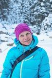一名微笑的远足者妇女的画象在冬天森林里 免版税库存照片