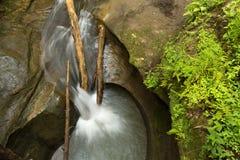 与小瀑布的美丽的光滑的流动的小河 免版税库存图片