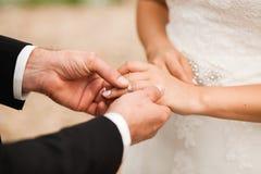 Νεόνυμφος που τίθεται στο γαμήλιο δαχτυλίδι Στοκ φωτογραφία με δικαίωμα ελεύθερης χρήσης