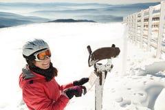 冬天滑雪胜地的少妇滑雪者在山读地图的,发现道路 免版税库存图片