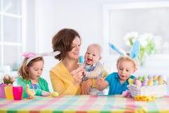 有绘复活节彩蛋的三个孩子的母亲 免版税库存图片