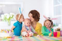 有绘复活节彩蛋的三个孩子的母亲 图库摄影
