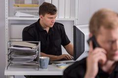 Полицейский используя компьютер на работе Стоковая Фотография