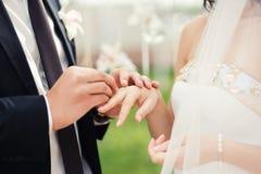 新郎和新娘在婚礼,关闭期间在交换圆环的手上 婚礼夫妇和室外婚礼 图库摄影