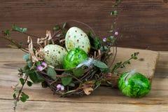 Φωλιά με τα χρωματισμένα αυγά Πάσχας στο ξύλινο υπόβαθρο Στοκ εικόνα με δικαίωμα ελεύθερης χρήσης