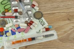昂贵的治疗的金钱 货币和药片 不同的颜色药片在金钱的 库存照片