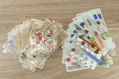 昂贵的治疗的金钱 货币和药片 不同的颜色药片在金钱的 真正欧洲钞票 图库摄影