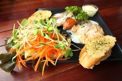烤牛排、香肠、蒜味面包和沙拉食谱 免版税库存照片
