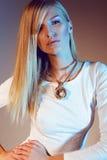白色礼服和金项链的美丽的女孩与长的白肤金发的直发 免版税图库摄影