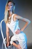 白色礼服和金项链的美丽的女孩与长的白肤金发的直发 免版税库存图片