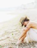 年轻镇静妇女放松坐沙子海海滩,浪漫有雾的早晨 库存图片