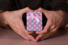 在拿着桃红色方格的礼物盒的心脏形状的两只男性手 免版税库存照片