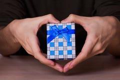 在拿着蓝色方格的礼物盒的心脏形状的两只男性手 库存照片
