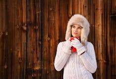 毛茸的帽子的沉思少妇有在土气木墙壁附近的杯子的 免版税图库摄影