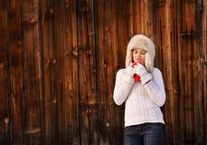 毛茸的帽子的沉思少妇有在土气木墙壁附近的杯子的 免版税库存图片