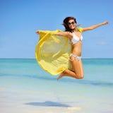 有跳跃在海滩的黄色围巾的美丽的女孩 旅行  免版税库存照片
