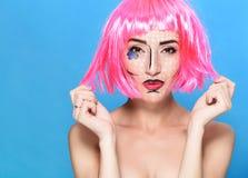 秀丽顶头射击 有创造性的流行艺术的少妇组成并且变粉红色看在蓝色背景的假发照相机 免版税库存照片