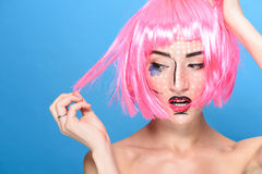 秀丽顶头射击 有创造性的流行艺术的少妇组成并且变粉红色看在蓝色背景的假发边 免版税库存照片