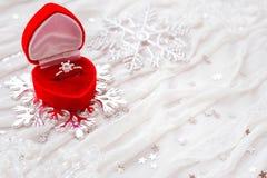 订婚在红色礼物盒的钻戒在白色织品 免版税库存照片