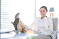 Εύθυμη επιχειρηματίας με τα πόδια στο γραφείο που εξετάζει τη κάμερα Στοκ Εικόνα